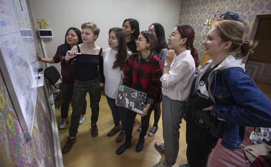 Eight female Kyrgyz scientists have a discussion around a whiteboard