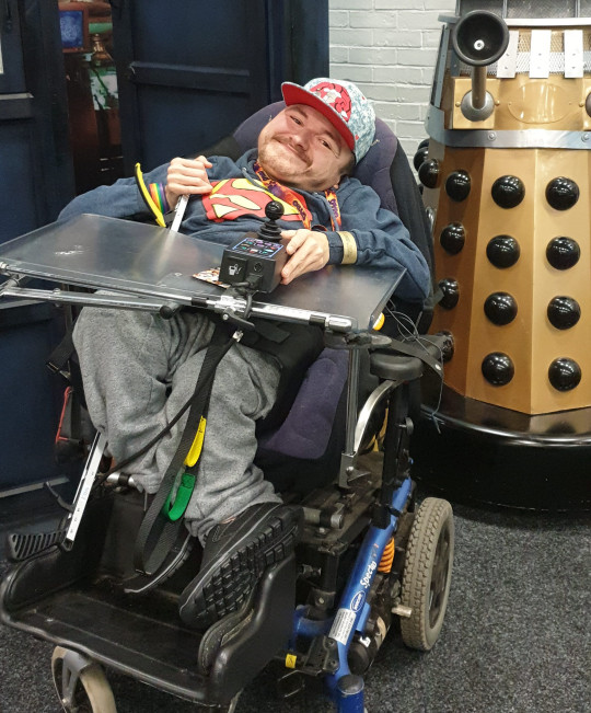 Chris Tomson in his wheelchair in front of a dalek