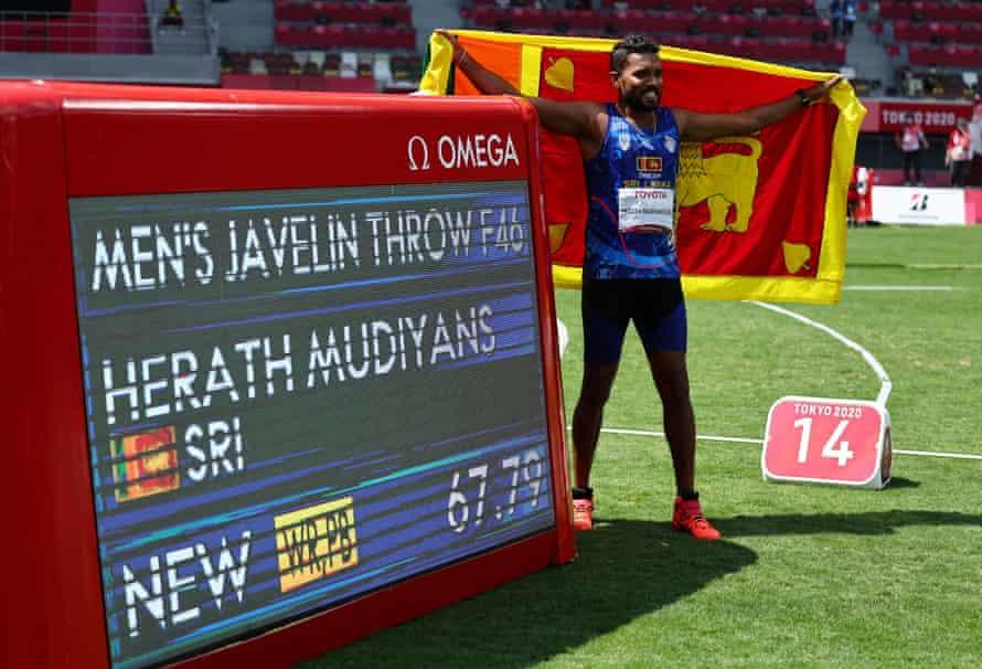 Gold medallist Dinesh Priyan. Herath Mudiyanselage of Sri Lanka celebrates next to a scoreboard after setting a new world record.