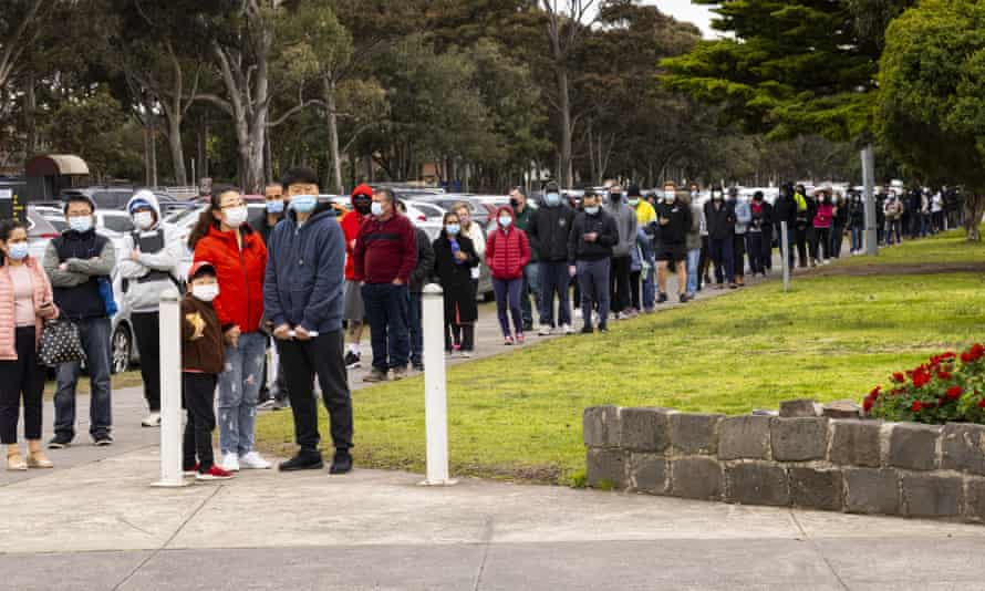 People line up for Covd vaccines at the Sandown Racecourse vaccination centre in Melbourne on Tuesday