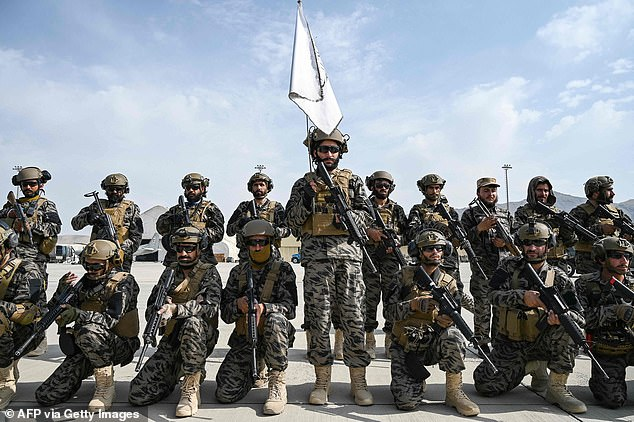 Taliban Badri special force fighters pose with American-made weapons under their white flag at Kabul airport today