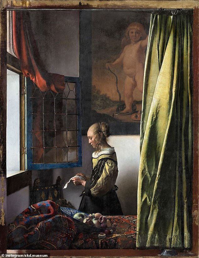 Hidden for centuries under a layer of paint, an image of Cupid in the background of a famous Johannes Vermeer masterpiece has finally been fully exposed to view (as pictured)