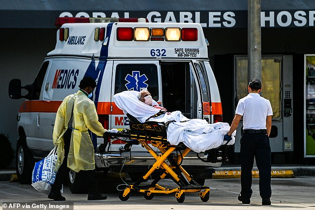 Covid patients are more likely to experience heart inflammation than patients for other conditions - or recipients of Covid vaccines - according to new CDC data. Pictured: Medics transfer a patient outside Coral Gables Hospital, near Miami, Florida, in August 2021