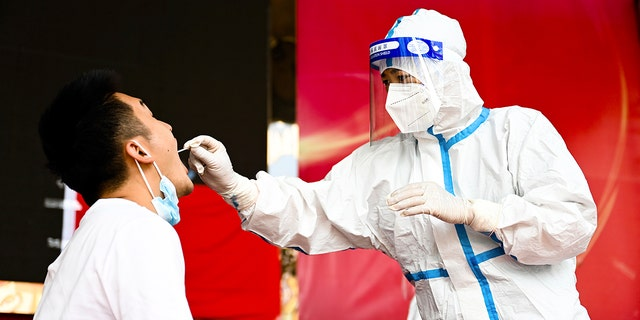 A medical worker collects a swab sample for nucleic acid test in Ruili City of southwest China's Yunnan Province on July 5, 2021. (Wang Guansen/Xinhua via AP, File)