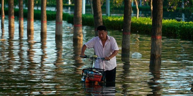 A man pushes a scooter through floodwaters in Xinxiang in central China's Henan Province, Monday, on July 26, 2021. (AP Photo/Dake Kang, File)