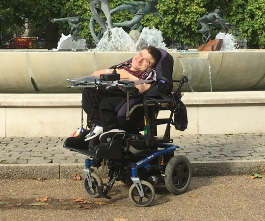 Chris Tomson in a wheelchair in front of a fountain