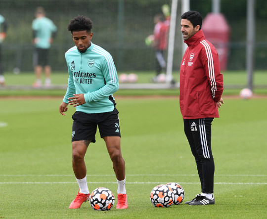 Reiss Nelson runs with the ball in Arsenal training