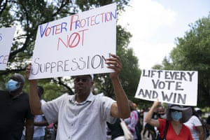 A man holds a sign that reads 'Voter Protection Not Suppression' to demonstrate for voting rights at the Texas Capitol.
