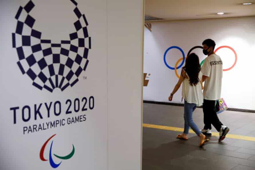 People walk by the Tokyo 2020 Paralympics logo at a metro station in Tokyo.