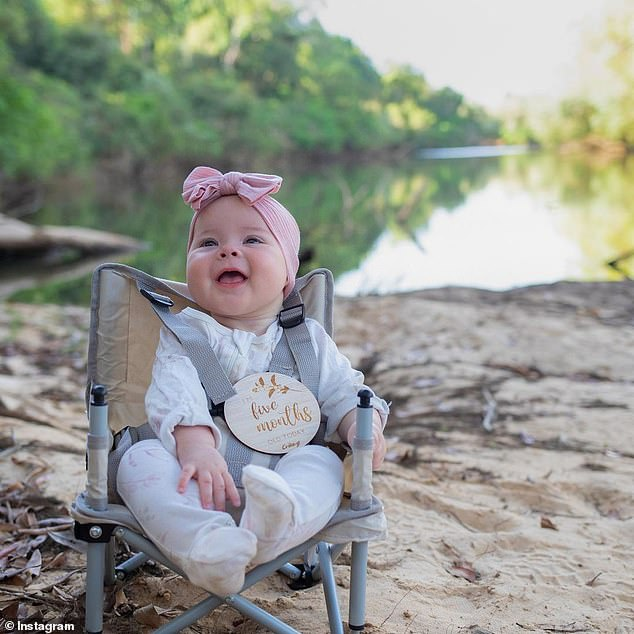 Cute! Bindi, 23, shared a series of photos of Grace smiling in a onesie with a pink bow on her head while strapped into her tiny camping chair next to a river