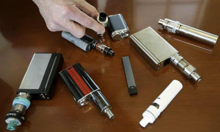 A high school principal in Massachusetts displays vaping devices that were confiscated from students in 2018.