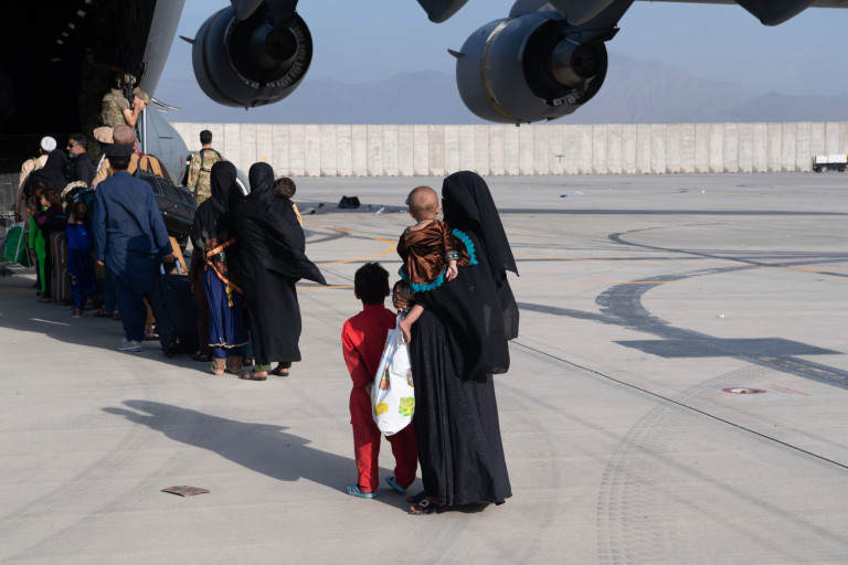 A woman stands on a runway, wearing a burqa, as she waits to get on an evacuation plane with her children