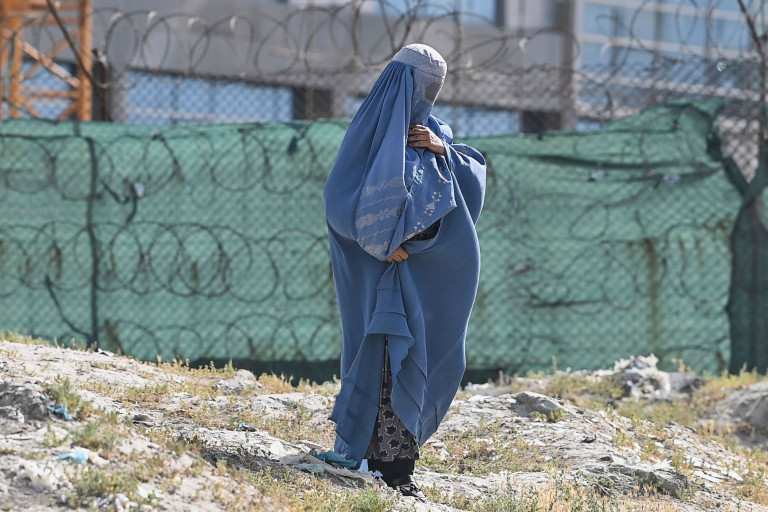 A woman wearing a blue-coloured burqa walks next to the construction site of a building in Kabul