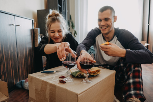 Cheerful Couple Having Food And Wine At Home