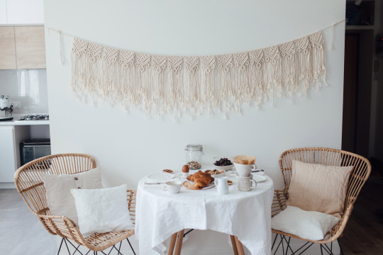 Morning elegant dining table with white linen tablecloth and served healthy breakfast on it