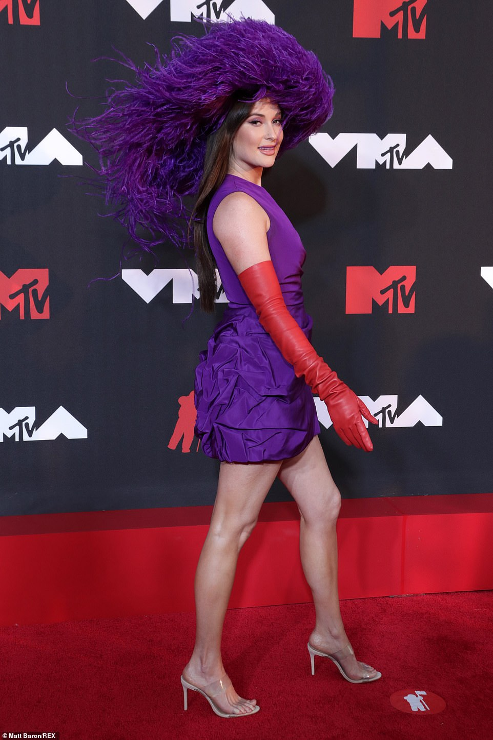 Charmer:Kacey Musgraves put a groovy twist on Southern Belle style wearing a fabulous feathered hat with a silk party dress and red leather opera gloves