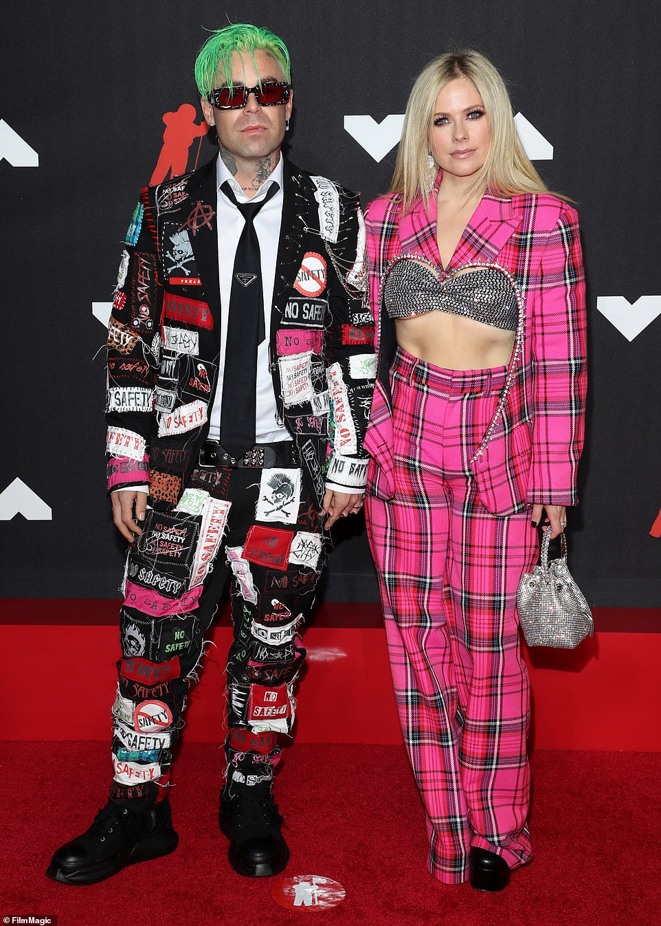 Pretty in pink:Avril Lavigne proved why she was a pop-punk princess wearing a pink plaid suit with a bedazzled bra while there with boyfriend Mod Sun