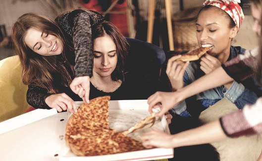 Four young women sitting round a table, eating pizza.