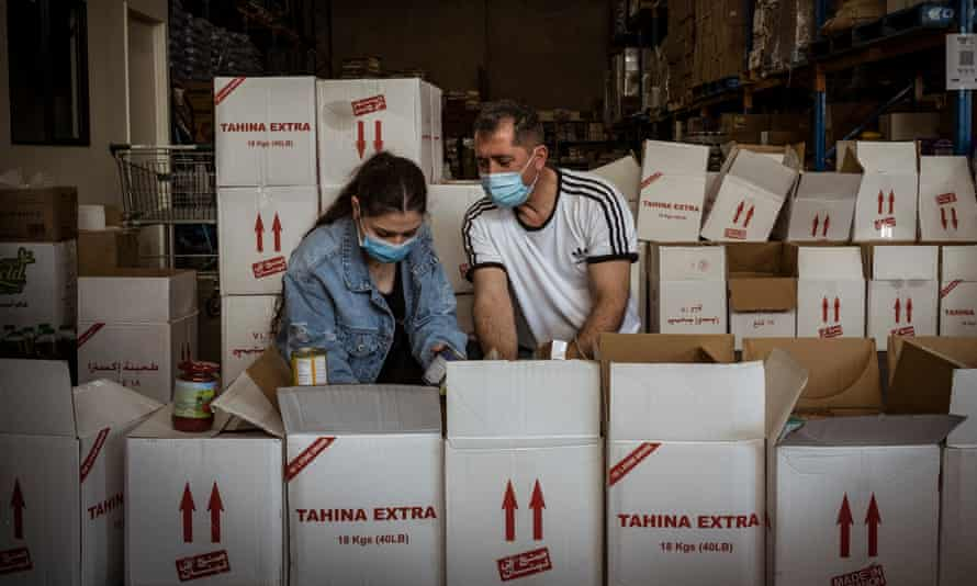 Volunteers Angel Barboura and her father Bashar, pack care packages for those isolating due to Covid-19 in Broadmedows