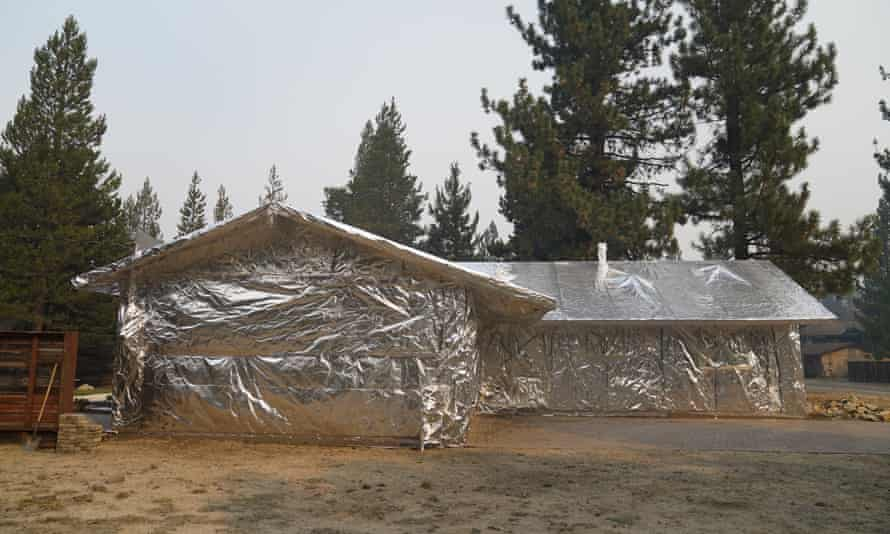 A home is completely wrapped in fire-resistant material in Meyers, California.