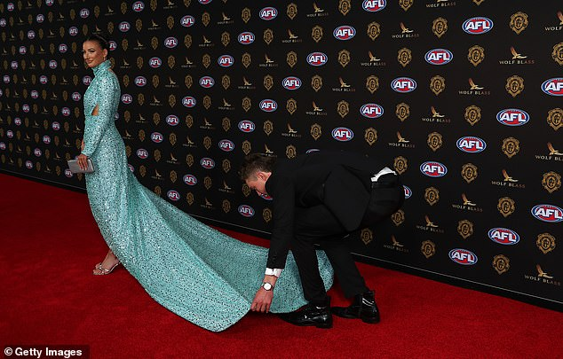 Chivalry isn't dead: Ever the gentleman, Patrick ensured Monique was red carpet-ready, pulling out the fabric of her dramatic train