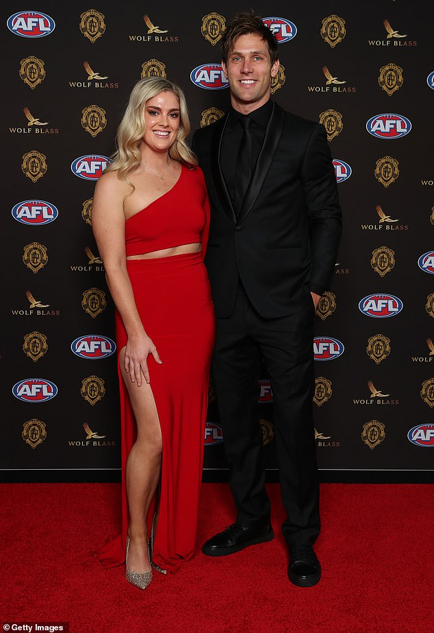 Racy: Matthew de Boer, 31, of the Greater Western Sydney Giants warmly embraced a beautiful Rachel Glascon who dared to bare in a racy red two-piece ensemble with a thigh split