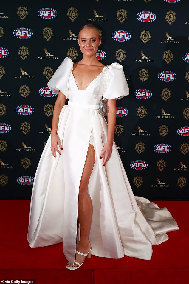 She's no wallflower: Also following the white memo was Georgia Mitchell, who donned a princess-style gown with a plunging neckline, oversized sleeves and a daring thigh split