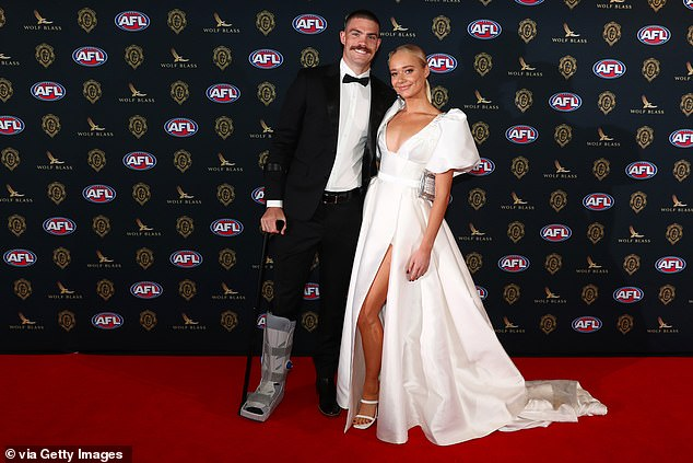 In great spirits: Georgia joined Sam Collins of the Gold Coast Suns, who didn't let a moon boot or cane dampen his spirits
