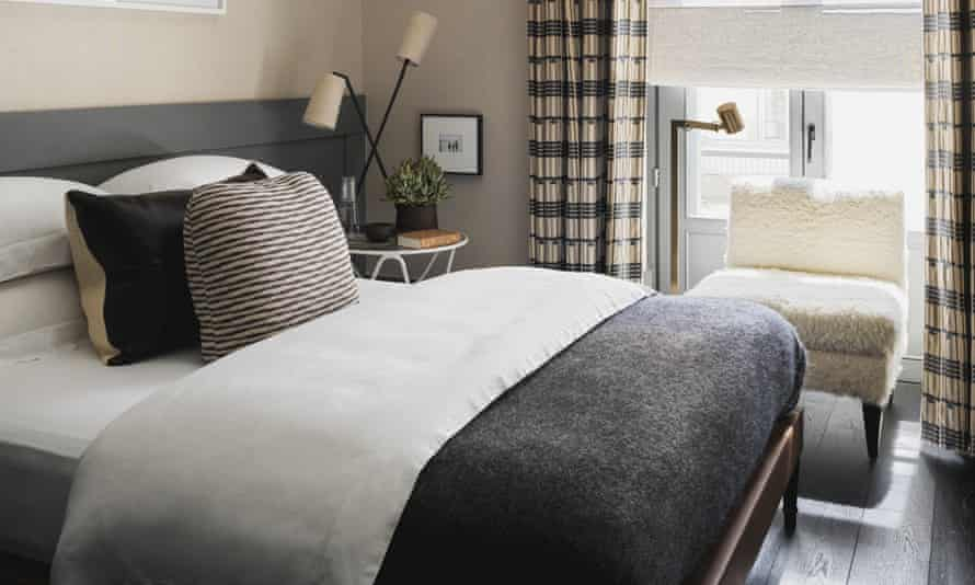 A bedroom with muted coloured bedding