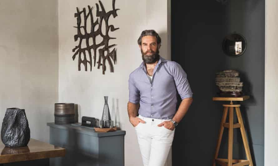 Rui Ribeiro leaning against a wall in his home, several art objects around him
