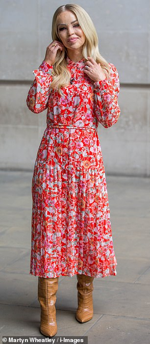 Stepping out in style: Katie looked effortlessly chic in a scarlet floral dress that she paired with slouchy brown boots