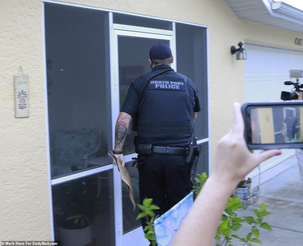 Police arrive with evidence bags at the North Port, Florida home of Brian Laundrie on Friday