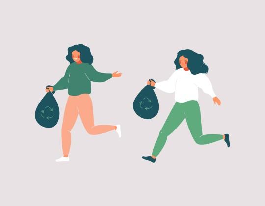 Cheerful women picking up trash while walking or Jogging.
