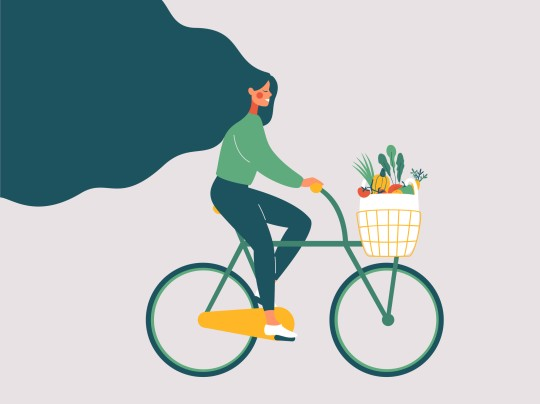 Young smiling girl with long hair riding bicycle with fresh vegetables in front basket.