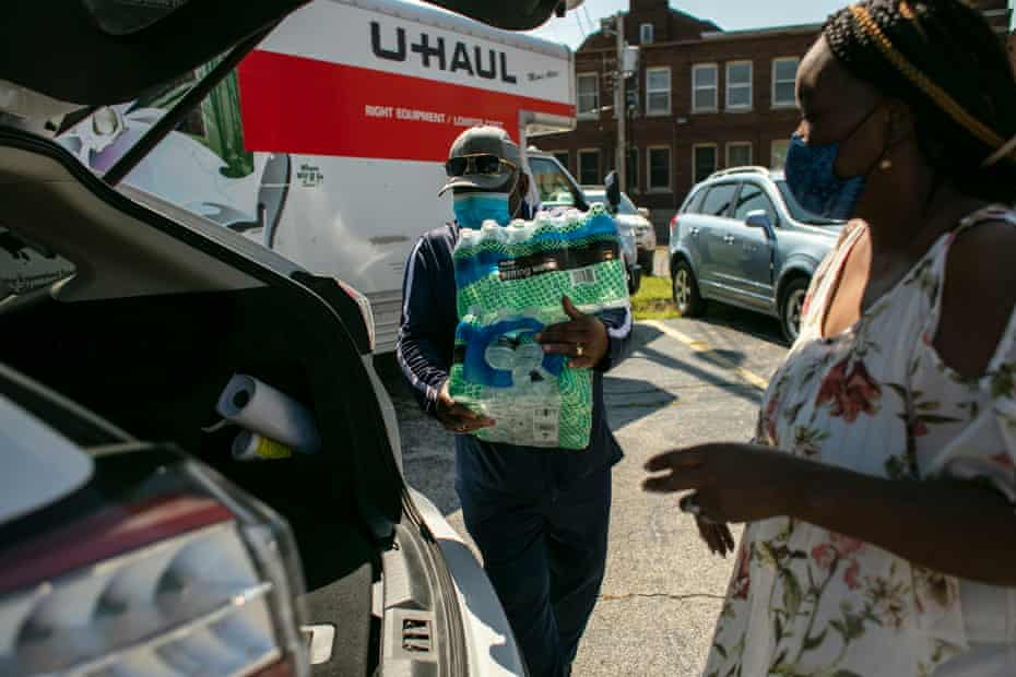 Volunteers load cases of water into residents' cars at the clean water giveaway at Pinkney's church.