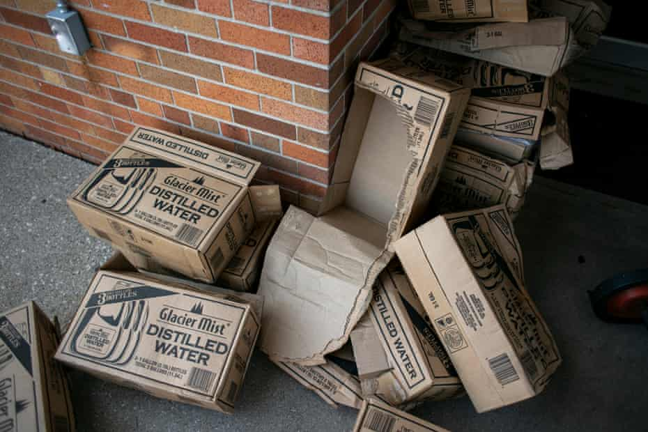 Discarded water boxes outside the clean water giveaway.