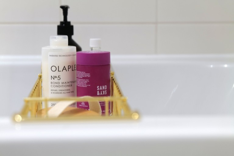 What I Rent: Georgia, £1,000 a month for a one-bedroom flat in Addlestone, Surrey - hair and body products in tray in the bath
