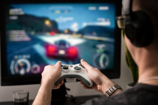 gaming game play tv fun gamer gamepad guy controller video console playing player holding hobby playful enjoyment view concept - stock image