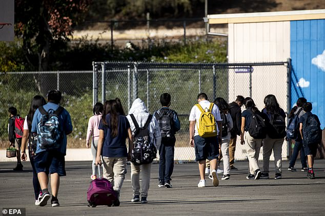 Out of more than 30,000 close contacts of COVID-19 patients, just 63 went on to contact the virus, equivalent to 0.2%. Pictured: Students walk to their classrooms at a middle school in El Sereno, East Los Angeles, September 10