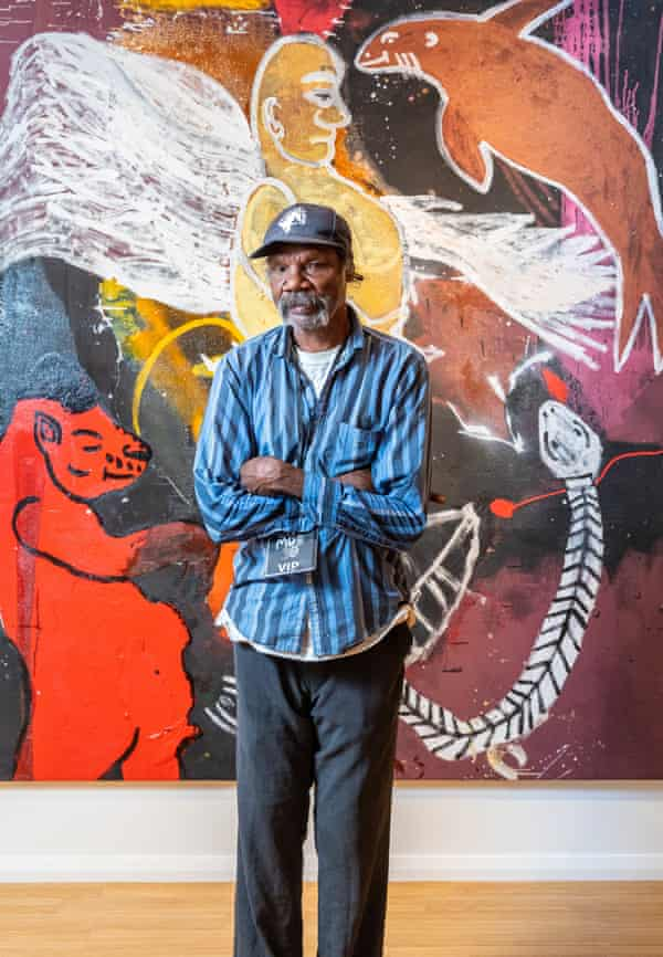 Fabian Brown, part of the 'Tennant Creek Brio' at Nyinkka Nyunyu Art & Culture Centre, in front of his painting for Desert Mob 30, Sad Angel with his creatures, The Divine Dolphin, and The Red Hippo.