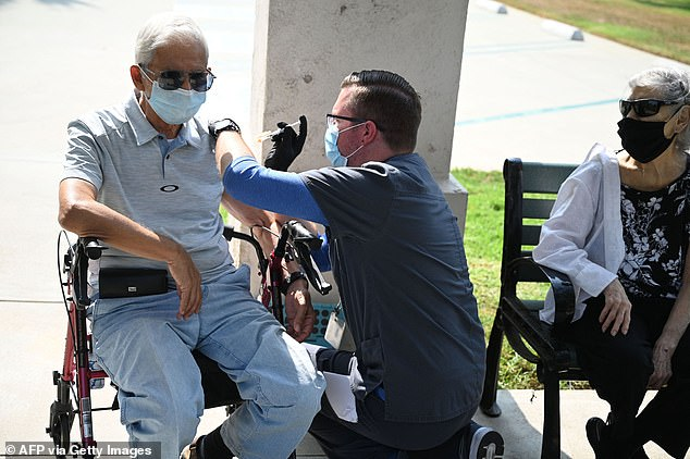 The CDC's advisory committee has voted to recommend boosters for use in those aged 65 and older and those with underlying medical conditions aged 50 to 64. Pictured: Nurse Kevin Grellman administers a third booster dose of Pfizer's vaccine to Jose Gomez, 80, after his wife Armida Gomez, 81, received hers in Pasadena, California, August 2021