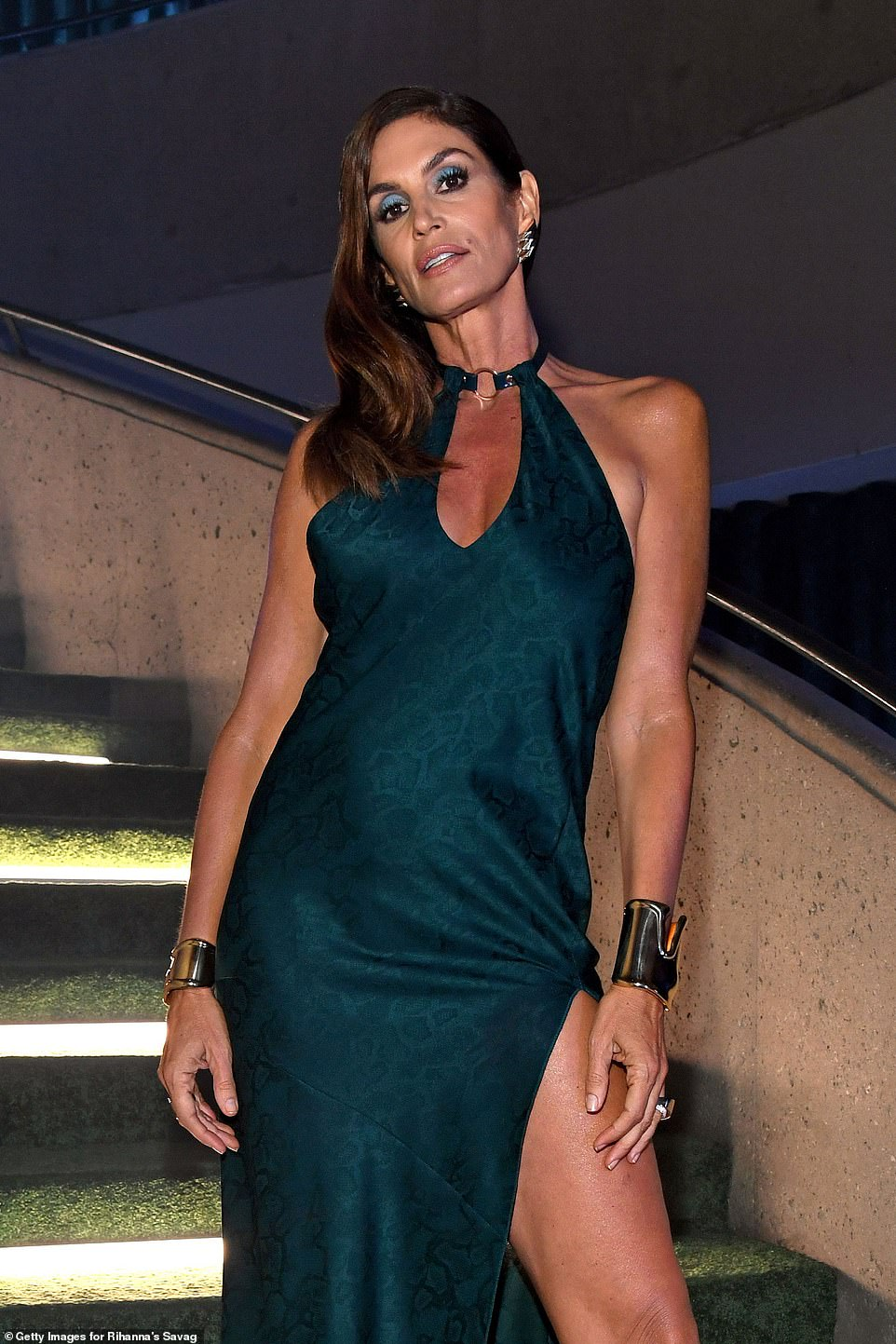 Timeless:Cindy Crawford looked undeniably glamorous in a satin floor-length gown with a dramatic leg slit