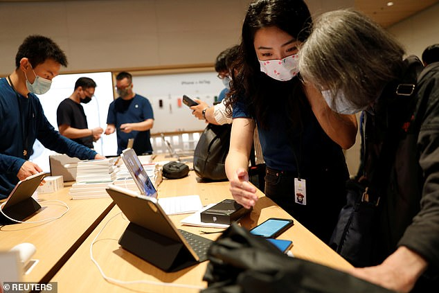 An Apple employee wearing a face mask speaks to a customer at an Apple Store in Beijing, China