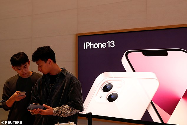 Customers stand in front of an image of iPhone 13 devices at an Apple Store on the day the new Apple iPhone 13 series goes on sale, in Beijing, China