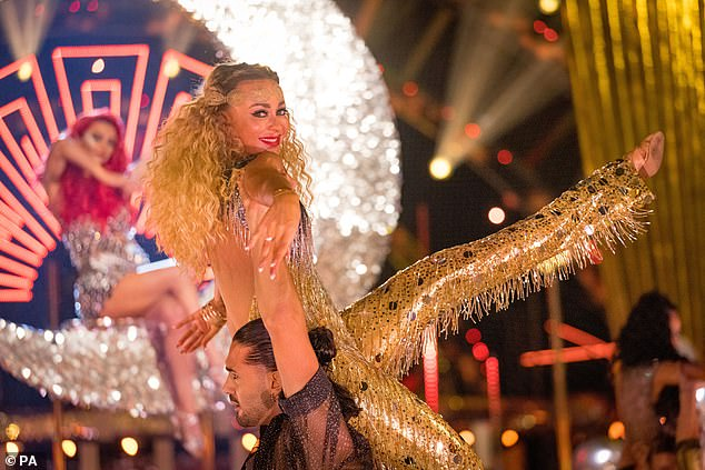 Golden girl:Luba Mushtuk was hoisted into the air while wearing a sequin tassel jumpsuit