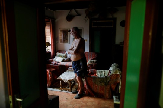 German resident, Gert Waegerle, 75, who was evacuated a week ago, stands inside his house after returning to it, following the eruption of a volcano on the Canary Island of La Palma, in Tacande de Arriba, Spain, September 27, 2021. Picture taken September 27, 2021. REUTERS/Jon Nazca