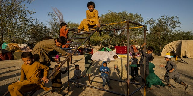 Afghan displaced children play at an internally displaced persons camp in Kabul, Afghanistan, on Monday.