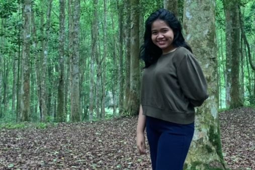 A woman standing in a forest surrounded by trees.