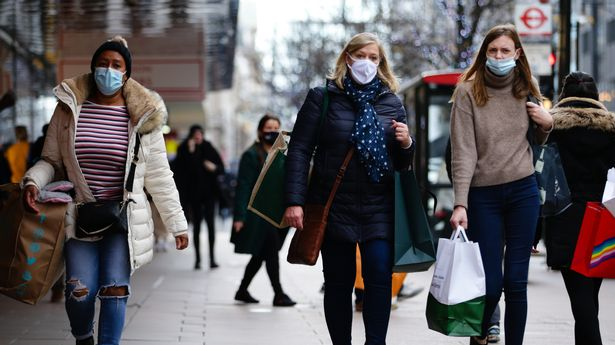 Shoppers wearing face masks carry bags along Oxford Street in London
