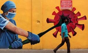 A man walks past a Covid-19 coronavirus awareness mural along the roadside in Chennai. Covid Awareness Mural in Chennai, Tamil Nadu, India.